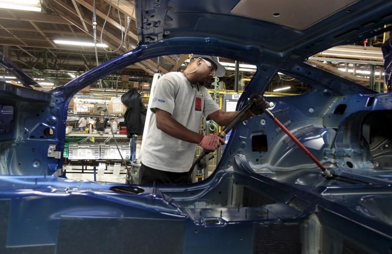 A Ford Motor assembly worker works on the frame of a 2015 Ford Mustang vehicle at the Ford Motor Flat Rock Assembly Plant in Flat Rock, Michigan