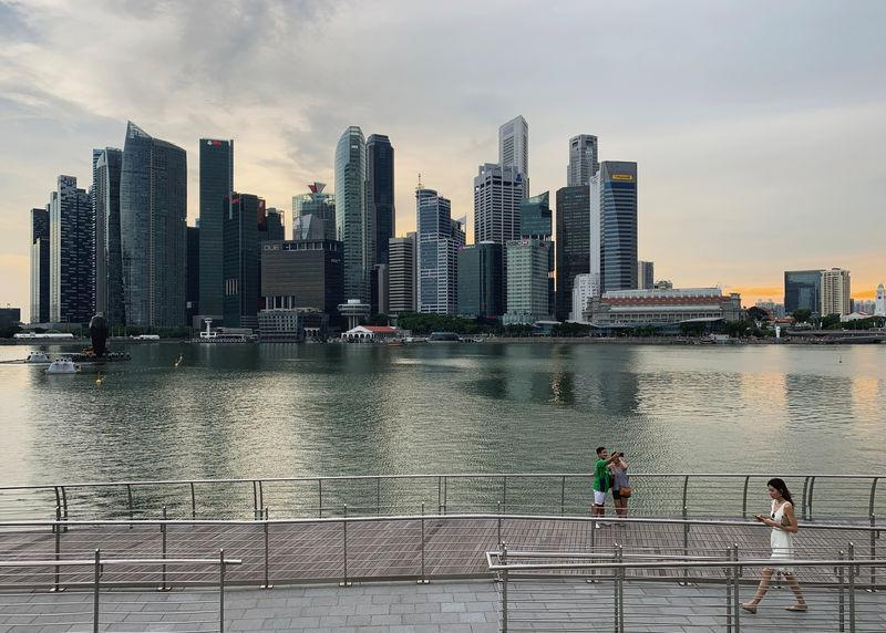FILE PHOTO: A passer-by looks at her mobile phone as people take a selfie photo using a smartphone, with Singapore's central business district skyline, in Singapore