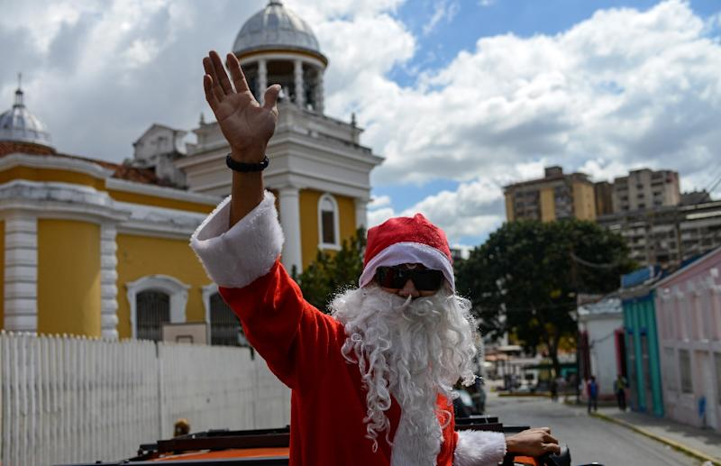 A man dressed as Santa Claus hands out food and clothes to the poor in Caracas, Venezuela (AFP Photo/FEDERICO PARRA)