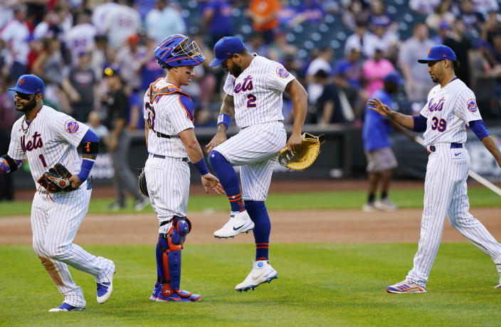 New York Mets catcher James McCann (33) slaps hands with left fielder Dominic Smith (2) as third baseman Jonathan Villar (1) and relief pitcher Edwin Diaz (39) leave the field after defeating the Atlanta Braves in the first baseball game of a doubleheader, Monday, June 21, 2021, in New York. (AP Photo/Kathy Willens)