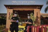 Police officers wearing masks stand in front of the H10 Costa Adeje Palace hotel in La Caleta, in the Canary Island of Tenerife, Spain, Wednesday, Feb. 26, 2020. Spanish officials say a tourist hotel on the Canary Island of Tenerife has been placed in quarantine after an Italian doctor staying there tested positive for the COVID-19 virus and Spanish news media says some 1,000 tourists staying at the complex are not allowed to leave. (AP Photo)