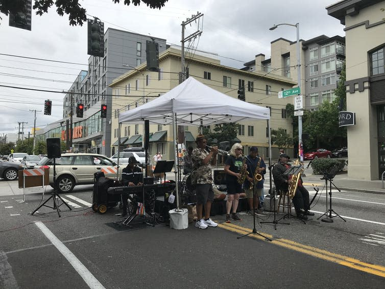 A band plays under a gazebo on a street closed to traffic.