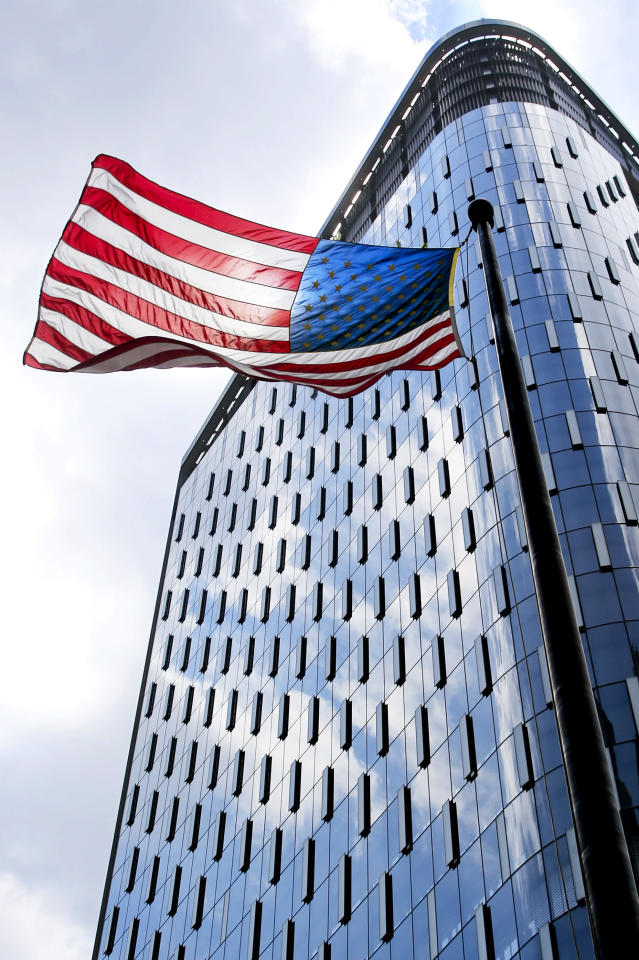 The sun shines through an American flag as it flies in front of the reflections of clouds in the windows of the Tower at PNC Plaza on Monday, July 17, 2017, in Pittsburgh. (AP Photo/Keith Srakocic)
