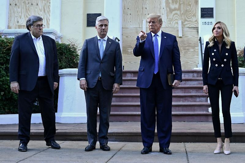 Donald Trump signals to a reporter to be quiet as he stands outside St John Episcopal Church following a walk from the nearby White House. Lafayette Park was cleared of protesters by police using tear gas so he could go there. He is flanked by Attorney General William Barr (far left), Chief of Staff Mark Meadows and Press Secretary Kayleigh McEnany: AFP via Getty Images