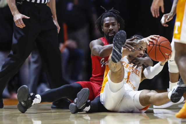 CORRECTS ID TO JACKSONVILLE STATE'S TY HUDSON, NOT JACKSON STATE GUARD TRISTAN JARRETT - Tennessee guard Lamonte Turner (1) keeps the ball from Jacksonville State guard Ty Hudson (4) during the first half of an NCAA college basketball game Saturday, Dec. 21, 2019, in Knoxville, Tenn. (AP Photo/Wade Payne)