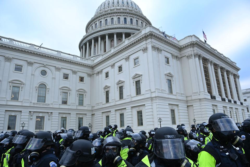 Police gather as Trump supporters clash with security forces as they storm the US Capitol in Washington, DC on January 6, 2021. - Thousands of Trump supporters, fueled by his spurious claims of voter fraud, flooded the nation's capital protesting the expected certification of Joe Biden's White House victory by the US Congress. (Photo by Brendan SMIALOWSKI / AFP) (Photo by BRENDAN SMIALOWSKI/AFP via Getty Images)