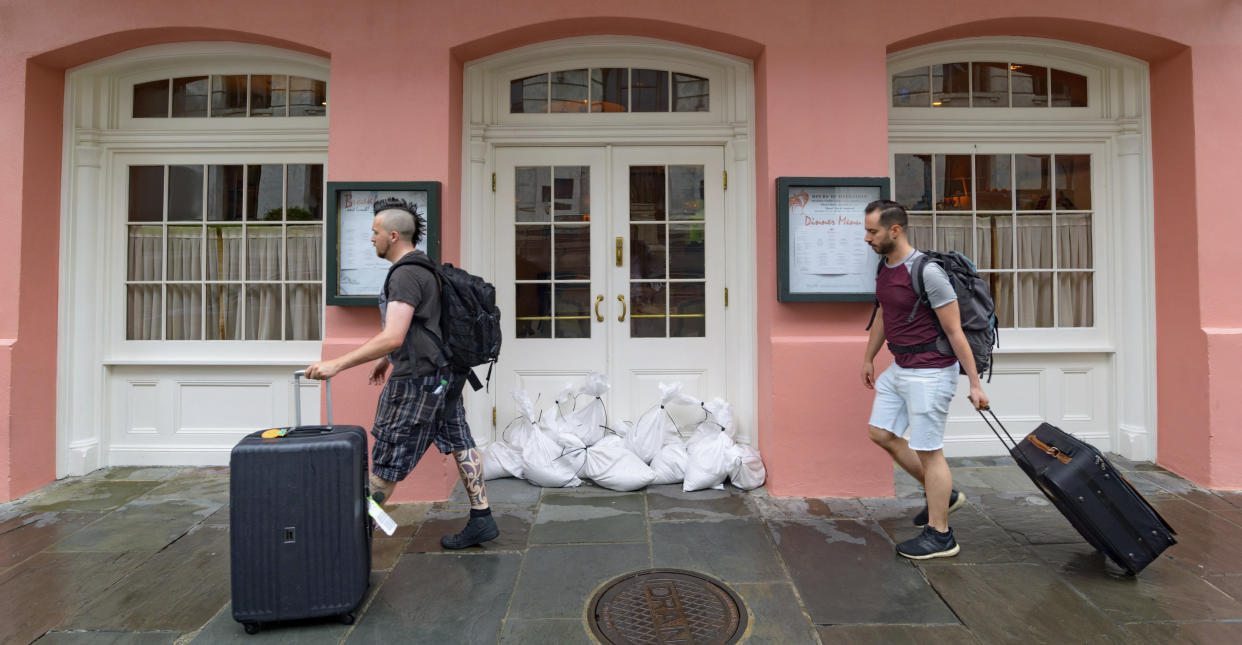 People walk past Brennan's restaurant in the French Quarter with sandbags on the front door as bands of rain from Tropical Storm Barry from the Gulf of Mexico move into New Orleans, La., Friday, July 12, 2019. (Photo: Matthew Hinton/AP)