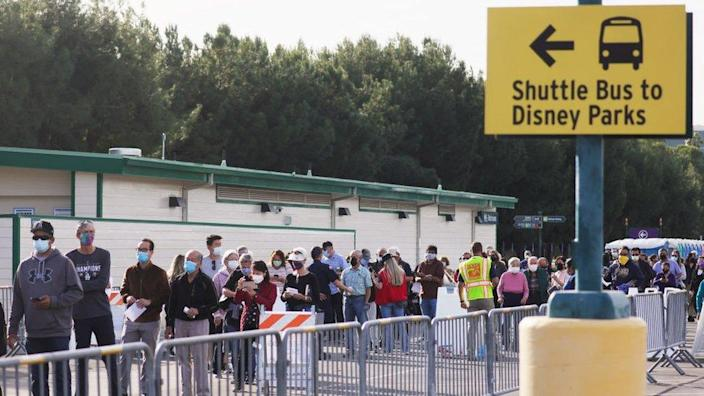 People wait in line to receive the Covid-19 vaccine at a mass vaccination site in a parking lot for Disneyland Resort