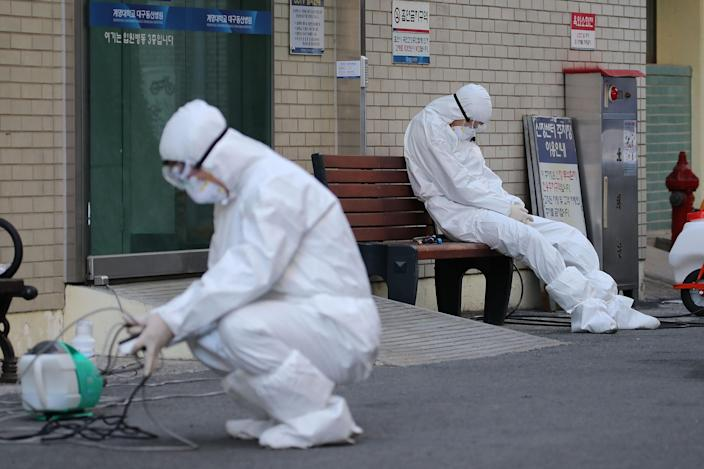 Image: A medical worker wearing protective gear takes a rest as he waits for ambulances carrying patients infected with the COVID-19 coronavirus at an entrance of a hospital in Daegu