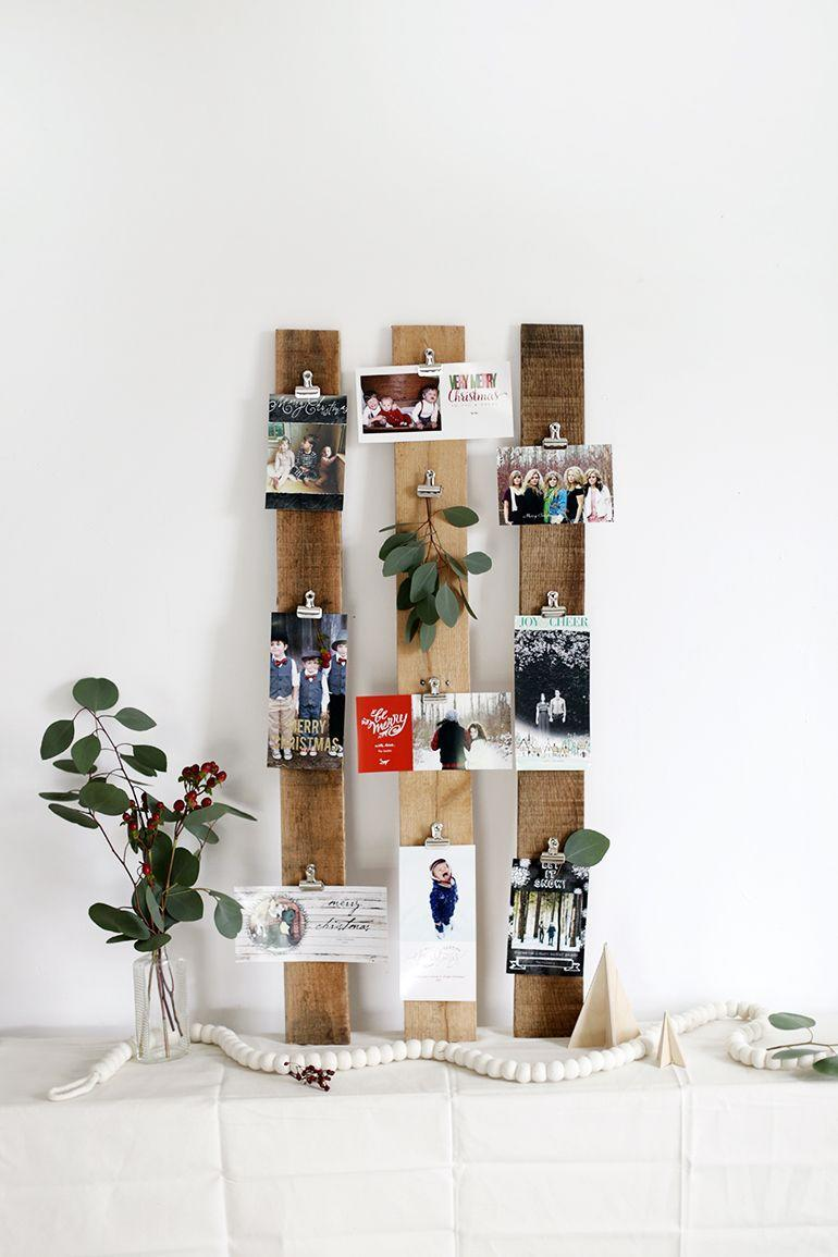 """<p>You don't have to go OTT with the festive themed decor. Simple wood planks with clips can hold your cards for a more minimalist approach. </p><p>Get the tutorial at <a href=""""https://themerrythought.com/diy/diy-christmas-card-display-2/"""" rel=""""nofollow noopener"""" target=""""_blank"""" data-ylk=""""slk:The Merry Thought"""" class=""""link rapid-noclick-resp"""">The Merry Thought</a>.</p>"""
