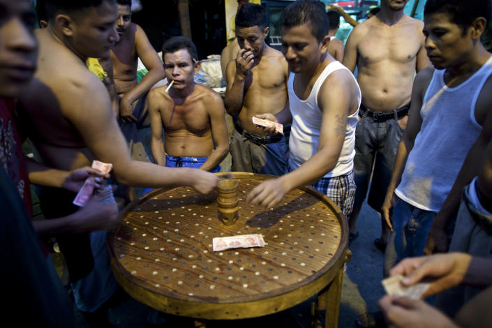 "In this May 3, 2012 photo, inmates make bets as they play a game of ""Chingolingo"" in San Pedro Sula Central Corrections Facility in San Pedro Sula, Honduras. Inside one of Honduras' most dangerous and overcrowded prisons, inmates operate a free-market bazaar, selling everything from iPhones to prostitutes. Guards do not cross into the inner sanctum controlled by prisoners, and prisoners do not breach the perimeter controlled by guards. (AP Photo/Rodrigo Abd)"