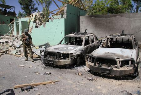 FILE PHOTO: A member of the Afghan security forces stands guard next to damaged army vehicles after a Taliban attack in Ghazni city, Afghanistan, August 15, 2018. REUTERS/Mustafa Andaleb/File Photo