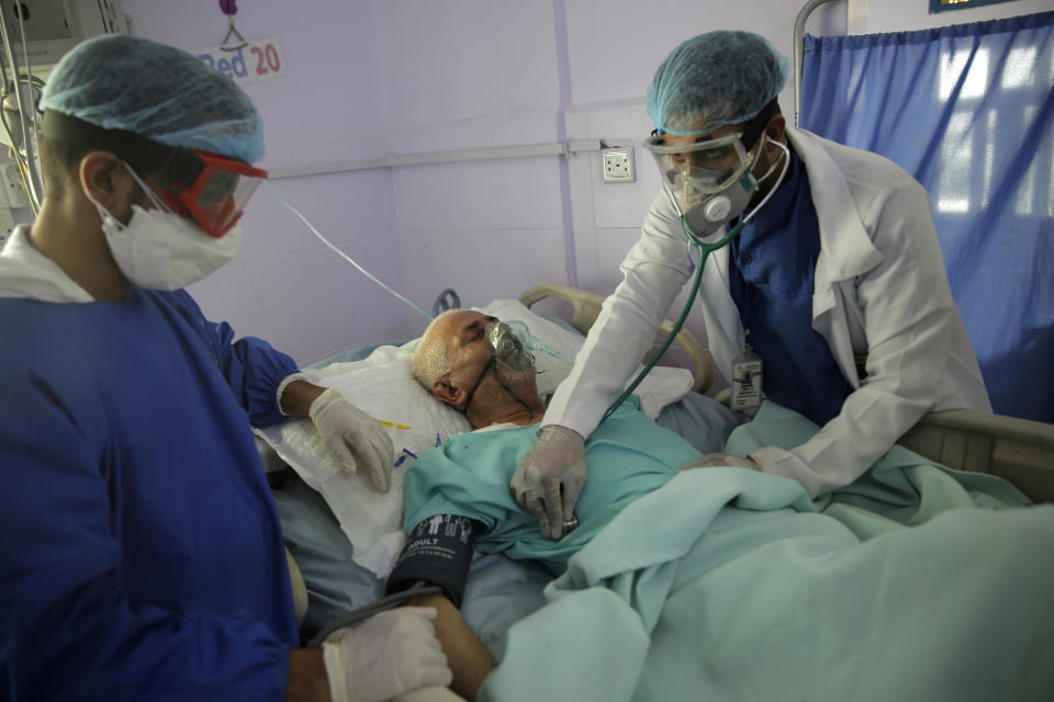 FILE - In this June 14, 2020, file photo, medical workers attend to a COVID-19 patient in an intensive care unit at a hospital in Sanaa, Yemen. A new snapshot of the frantic global response to the coronavirus pandemic shows some of the world's largest government donors of humanitarian assistance are buckling under the strain and overall aid commitments have dropped by a third from the same period last year. (AP Photo/Hani Mohammed, File)