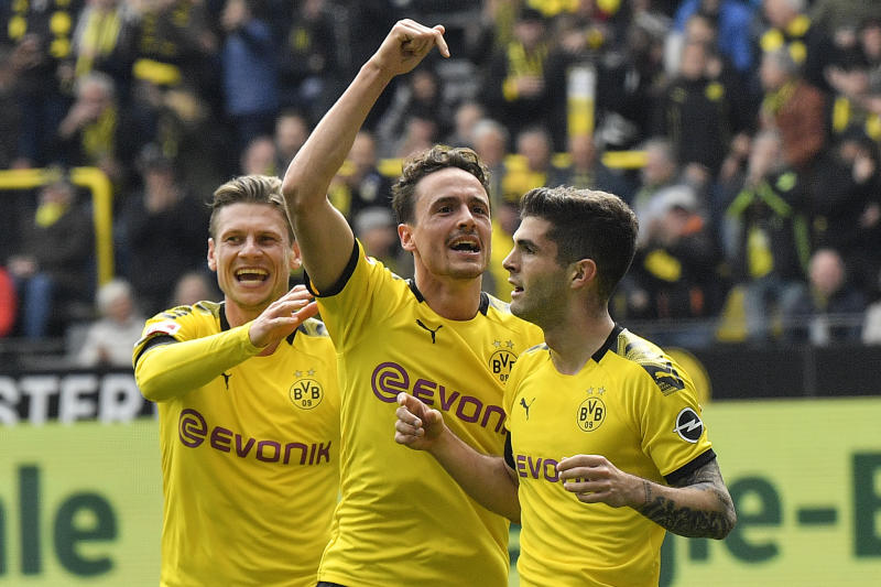 Dortmund's Christian Pulisic celebrates his opening goal with Thomas Delaney and Lukasz Piszczek, from right, during the German Bundesliga soccer match between Borussia Dortmund and Fortuna Duesseldorf in Dortmund, Germany, Saturday, May 11, 2019. (AP Photo/Martin Meissner)