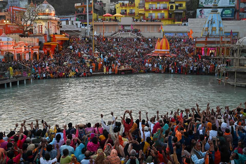 TOPSHOT - Hindu devotees attend evening prayers after taking a holy dip in the waters of the River Ganges on the Shahi Snan (grand bath) on the occasion of the Maha Shivratri festival during the ongoing religious Kumbh Mela festival in Haridwar on March 11, 2021. (Photo by Prakash SINGH / AFP) (Photo by PRAKASH SINGH/AFP via Getty Images)