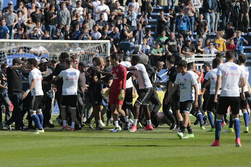 Stewards and Lyon staff members try to stop Bastia's supporters who invade the pitch to fight with Lyon players during warm up prior to the French L1 Football match between Bastia (SCB) and Lyon (OL) on April 16, 2017, at the Armand Cesari stadium, in Bastia, on the French Mediterranean island of Corsica. / AFP PHOTO / PASCAL POCHARD-CASABIANCA