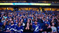Tampa Bay Lightning fans at a watch party at Amalie Arena, in Tampa, Fla., look on in disbelief as their team loses in overtime in Montreal to the Montreal Canadiens in Game 4 of the NHL hockey Stanley Cup final, Monday, July 5, 2021. (Luis Santana/Tampa Bay Times via AP)