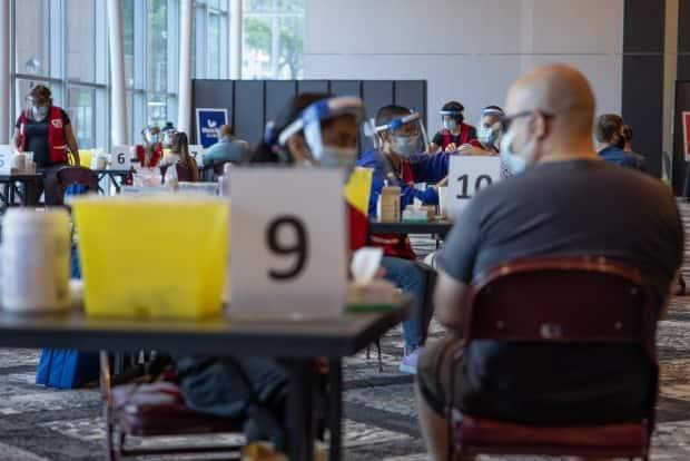 People are shown receiving vaccinations at the Halifax Convention Centre's walk-in clinic. (Robert Short/CBC - image credit)