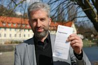 Tuebingen's mayor Boris Palmer shows his Tagesticket or day pass