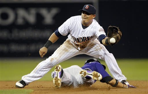 San Diego Padres shortstop Everth Cabrera can't handle the throw, as Colorado Rockies' Carlos Gonzalez, below, steals second base during the seventh inning of their baseball game in San Diego, Calif., Friday, Sept. 14, 2012. (AP Photo/Alex Gallardo)