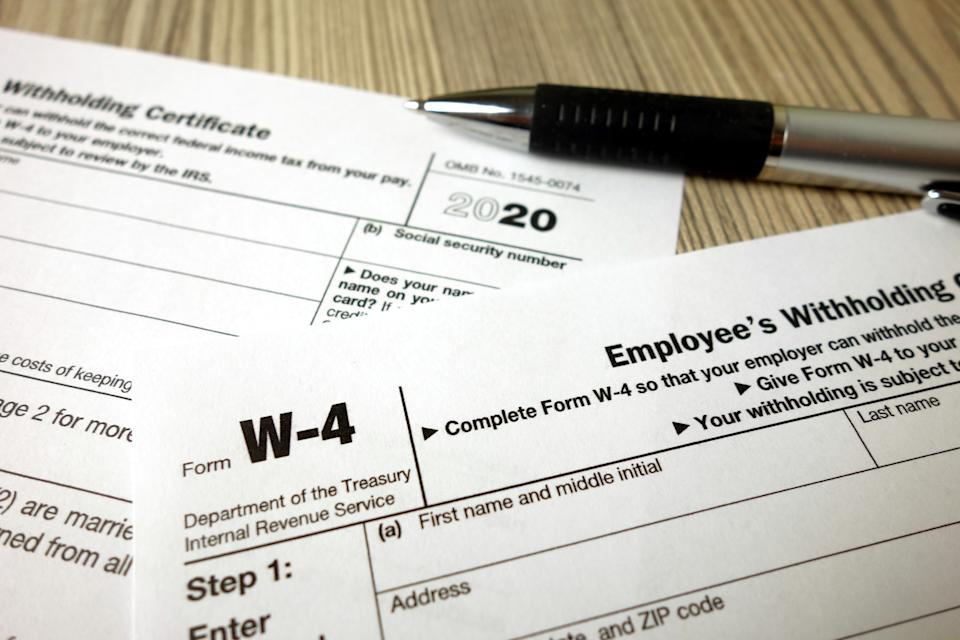 Blank W-4 form and a pen. Tax season concept