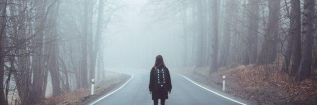 woman standing in road in the middle of foggy woods