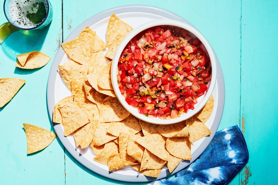 """A simple salsa that makes use of your grill. Serve with tortilla chips—and <a href=""""https://www.epicurious.com/recipes/food/views/margarita-242524?mbid=synd_yahoo_rss"""" rel=""""nofollow noopener"""" target=""""_blank"""" data-ylk=""""slk:margaritas"""" class=""""link rapid-noclick-resp"""">margaritas</a> or <a href=""""https://www.epicurious.com/recipes/food/views/paloma-51140240?mbid=synd_yahoo_rss"""" rel=""""nofollow noopener"""" target=""""_blank"""" data-ylk=""""slk:palomas"""" class=""""link rapid-noclick-resp"""">palomas</a>. Then whip up some <a href=""""https://www.epicurious.com/recipes-menus/best-taco-recipes-gallery?mbid=synd_yahoo_rss"""" rel=""""nofollow noopener"""" target=""""_blank"""" data-ylk=""""slk:tacos"""" class=""""link rapid-noclick-resp"""">tacos</a> for your main course. <a href=""""https://www.epicurious.com/recipes/food/views/3-ingredient-grilled-and-fresh-tomato-salsa?mbid=synd_yahoo_rss"""" rel=""""nofollow noopener"""" target=""""_blank"""" data-ylk=""""slk:See recipe."""" class=""""link rapid-noclick-resp"""">See recipe.</a>"""