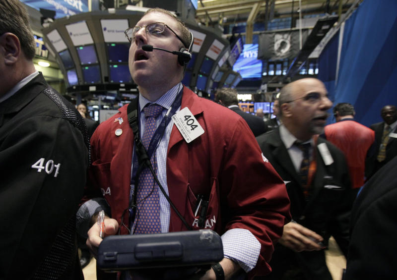 In a May 3, 2012, photo, trader Ryan Falvey, left, works on the floor of the New York Stock Exchange.  Wall Street is poised to open lower with Dow futures and the S&P 500 futures both 0.7 percent lower.   (AP Photo/Richard Drew)