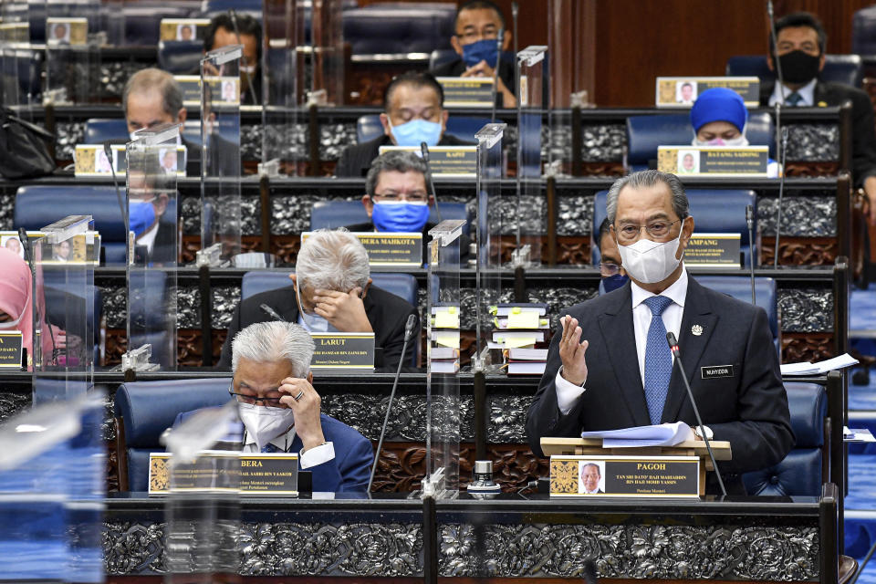 In this photo released by Malaysia's Department of Information, Malaysia's Prime Minister Muhyiddin Yassin wearing a face mask to help curb the spread of the coronavirus speaks at the parliamentary session at parliament house in Kuala Lumpur, Monday, July 26, 2021. Malaysia's government said it will not extend a coronavirus emergency beyond August 1 as Parliament reopened Monday after a disputed seven-month suspension amid a worsening pandemic. (Famer Roheni/ Malaysia's Department of Information via AP)