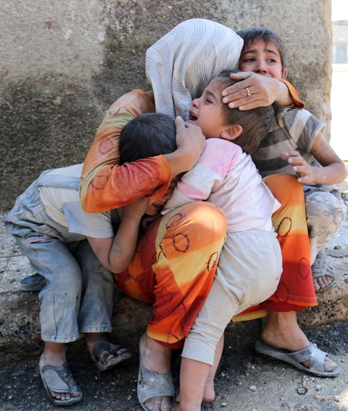 A Syrian woman comforts her children after their house in the Sahour nieghbourhood of the northern Syrian city of Aleppo was bombed on May 14, 2014 (AFP Photo/Zein al-Rifai)