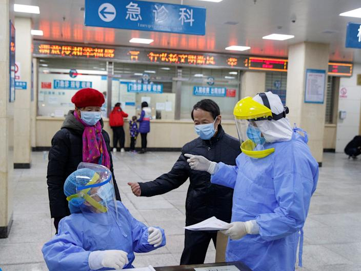 Nurses in protective clothing talk to people in the reception area of ​​the First People's Hospital in Yueyang, Hunan Province, China on January 28, 2020.