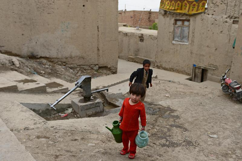 An Afghan child carries water from a well in Kabul on April 22, 2013