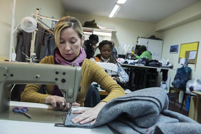 In this Monday, Jan. 30, 2017, a migrant sews a blanket, at a tiny coat workshop charity called Naomi in the northern Greek city of Thessaloniki, which is working long hours to collect and wash discarded blankets and turn them into wearable coats. The blankets are mostly army issue gray with red stitching and are distributed as aid at the sprawling refugee and migrant encampments, and are being recycled into practical coats for the vulnerable refugees who are facing a harsh winter. (AP Photo/Giannis Papanikos)
