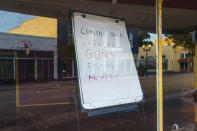 A sign stands in a vacant storefront window in Palatka, Fla., Tuesday, April 13, 2021. The town, with a population split almost equally between Black and white, had been devastated by the 2008 Great Recession. Many of its prized murals were fading, and there were more shuttered shops in the old downtown than open. (AP Photo/David Goldman)