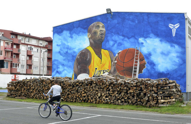 A boy rides a bicycle in front of a new tribute mural honoring former Los Angeles Lakers star Kobe Bryant who was killed in a helicopter crash on Jan. 26, on the school building in Bosanska Gradiska, Bosnia, Wednesday, June 3, 2020. (AP/Radivoje Pavicic)