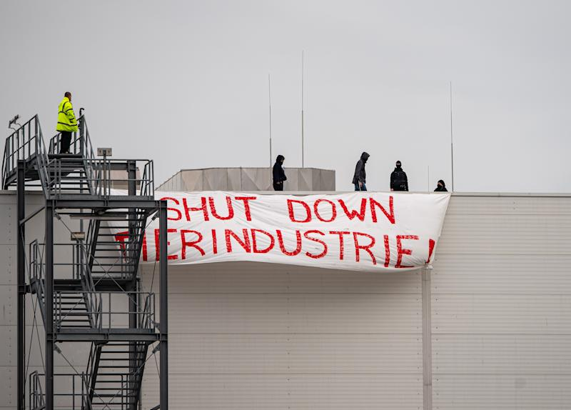"""dpatop - 04 July 2020, North Rhine-Westphalia, Rheda-Wiedenbrück: Four activists of the """"Alliance Together Against the Animal Industry"""" occupied a roof of the Tönnies company and hung up a banner from there with the inscription: """"SHUT DOWN ANIMAL INDUSTRY"""". On the left, an employee of Tönnies Security is standing on the staircase to the roof. Photo: Guido Kirchner/dpa (Photo by Guido Kirchner/picture alliance via Getty Images)"""