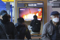 """People watch a TV screen showing a file image of North Korea's missile launch during a news program at the Seoul Railway Station in Seoul, South Korea, Sunday, March 29, 2020. North Korea on Sunday fired two suspected ballistic missiles into the sea, South Korea said, calling it """"very inappropriate"""" at a time when the world is battling the coronavirus pandemic.(AP Photo/Ahn Young-joon)"""
