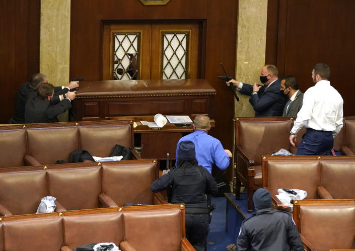 U.S. Capitol police officers point their guns at a door that was vandalized in the House Chamber during a joint session of Congress. (Drew Angerer/Getty Images)