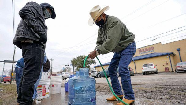 PHOTO: Leovardo Perez, right, fills a water jug using a hose from a public park water spigot, Feb. 18, 2021, in Houston. (David J. Phillip/AP)