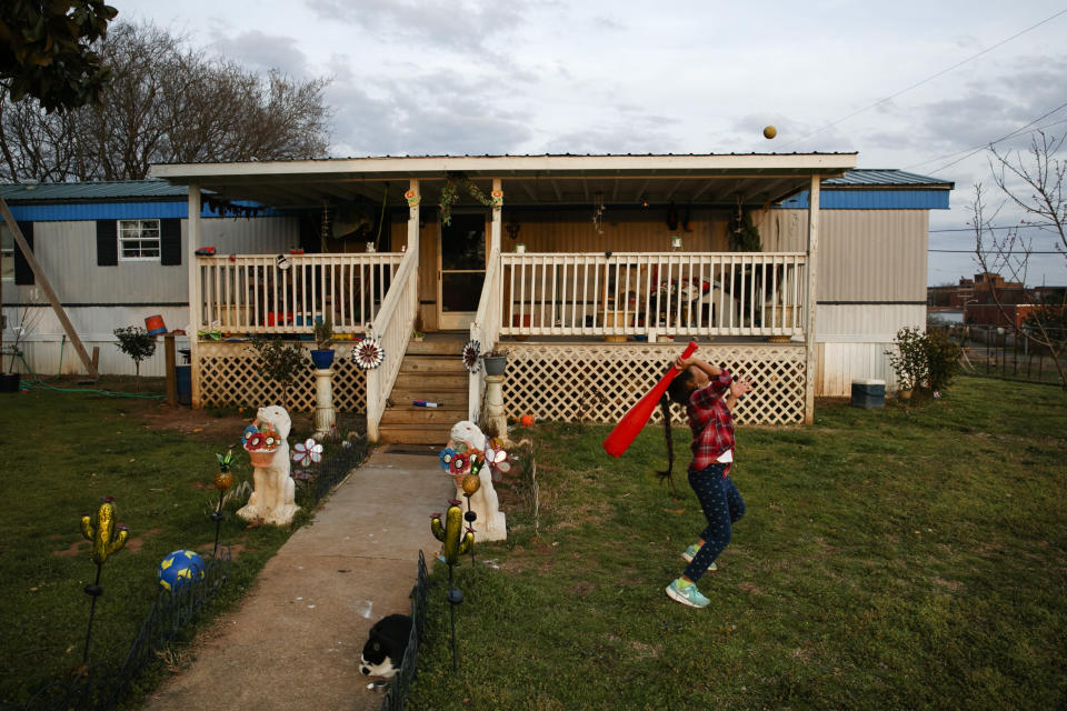 Dulce, 6, plays in the yard of their family home across the railroad tracks in Burlington, N.C., Monday, March 9, 2020. (AP Photo/Jacquelyn Martin)