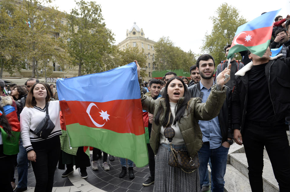 Azerbaijanis celebrate waving national flags in Baku, Azerbaijan, Tuesday, Nov. 10, 2020. Armenia and Azerbaijan announced an agreement early Tuesday to halt fighting over the Nagorno-Karabakh region of Azerbaijan under a pact signed with Russia that calls for deployment of nearly 2,000 Russian peacekeepers and territorial concessions. (AP Photo)
