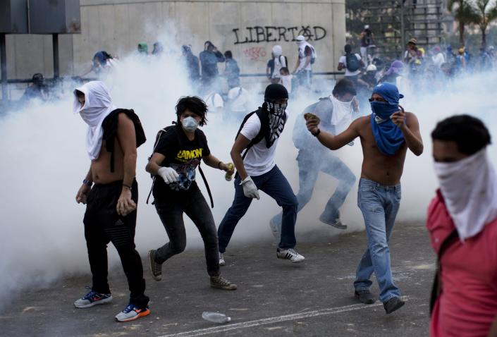 A group of masked men run for cover after riot police launched tear gas in Caracas, Venezuela, Saturday, Feb. 22, 2014. After an opposition rally broke up in the late afternoon, in a pattern that has been seen in past demonstrations about 1,000 stragglers erected barricades of trash and other debris and threw rocks and bottles at police and National Guardsmen. The troops responded with volleys of tear gas to prevent the students from reaching a highway and blocking traffic. (AP Photo/Rodrigo Abd