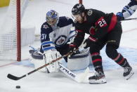 Ottawa Senators right wing Connor Brown (28) tries to put the puck past Winnipeg Jets goaltender Connor Hellebuyck during second-period NHL hockey game action Monday, April 12, 2021, in Ottawa, Ontario. (Adrian Wyld/The Canadian Press via AP)
