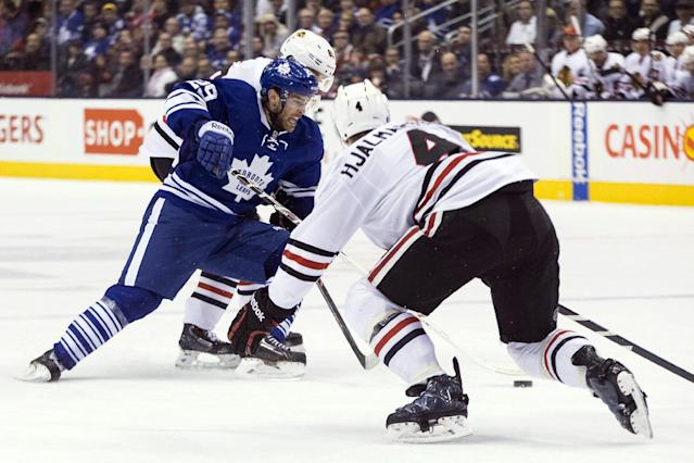 Toronto Maple Leafs' Jerry D'Amigo, left, battles for the puck with Chicago Blackhawks' Marian Hossa, back, as Niklas Hjalmarsson covers during the second period of an NHL hockey game in Toronto on Saturday, Dec. 14, 2013. (AP Photo/The Canadian Press, Chris Young)