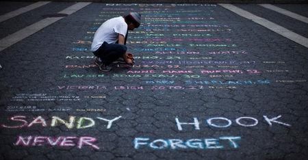 FILE PHOTO:    Street artist Mark Panzarino, 41, prepares a memorial as he writes the names of the Sandy Hook Elementary School victims during the six-month anniversary of the massacre, at Union Square in New York, June 14, 2013. REUTERS/Eduardo Munoz/File Photo