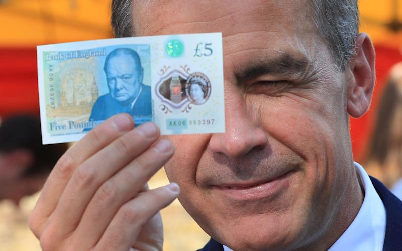 Bank of England Governor Mark Carney inspects the new plastic £5 note but does not spot incorrect grammar -  Jonathan Brady