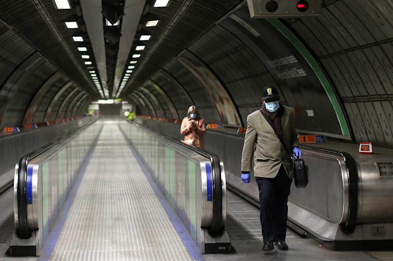 "People wearing PPE (personal protective equipment), including face masks as a precautionary measure against COVID-19, walk to take a London Underground Tube train in the evening rush hour at Waterloo station on May 11, 2020, as life in Britain continues during the nationwide lockdown due to the novel coronavirus pandemic. - The British government on Monday published what it said was a ""cautious roadmap"" to ease the seven-week coronavirus lockdown in England, notably recommending people wear facemasks in some public settings. But the devolved governments in Scotland and Wales have opted for a more cautious approach, keeping the strictest stay-at-home measures in place to contain the outbreak. (Photo by ISABEL INFANTES / AFP) (Photo by ISABEL INFANTES/AFP via Getty Images)"