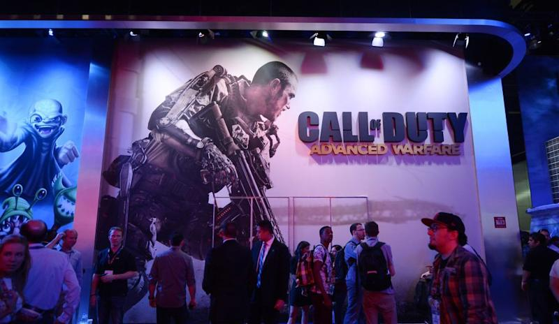 """Attendees walk pass a giant billboard promoting the new multiplayer action game """"Call of Duty: Advanced Warfare"""""""
