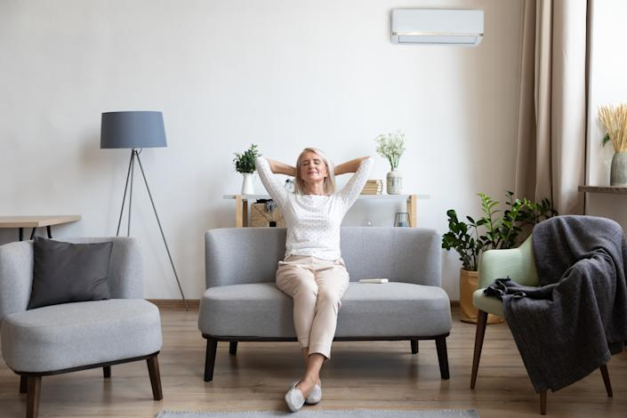 Relaxed satisfied older woman sitting leaning back on couch in air conditioner room, happy peaceful mature female with hands behind head resting on sofa at home, enjoying fresh air, breathing