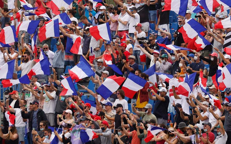 Formula One F1 - French Grand Prix - Circuit Paul Ricard, Le Castellet, France - June 20, 2021 General view of fans in the stands waving flags of France before the race - REUTERS/Eric Gaillard